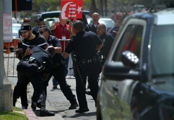 A protester is tackled by Los Angeles Police officers after trying to access Turkish supporters during a march by Armenian supporters outside the Turkish Consulate in Los Angeles