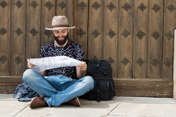 A tourist sitting and reading a map while listening to music