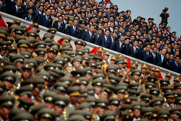 A soldier films North Korean soldiers, officers and high ranking officials attending a military parade marking the 105th birth anniversary of country's founding father in Pyongyang