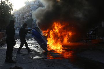 A man tries to put out a fire at a site hit by airstrikes in the rebel-controlled town of Ariha in Idlib province