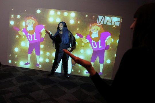 """A woman participates in the """"Pop n' Lock Dance Machine""""  installation at the Brooklyn Academy of Music  in Brooklyn, New York"""