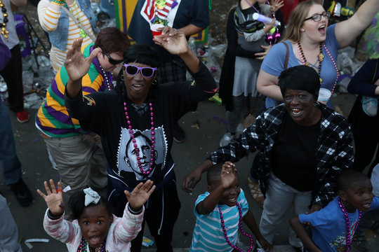 People watch as floats make their way during the Bacchus parade at Mardi Gras in New Orleans, Louisiana
