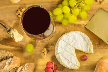 Red wine, cheese, bread, and grapes, overhead photo