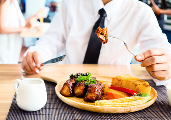 Close up of woman hand holding fork while eating rib steak on wooden tray at restaurant.