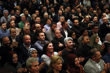 People listen as Turkish Economy Minister Nihat Zeybekci makes a speech in Cologne
