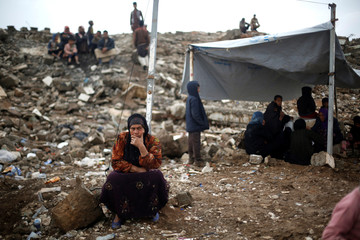 A displaced Iraqi woman who fled her home waits outside Hammam al-Alil camp south of Mosul