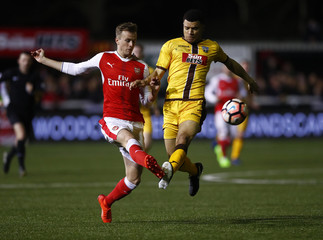 Arsenal's Rob Holding in action with Sutton United's Maxime Biamou