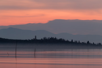 An island at sunset, with beautiful red and orange reflections on water, and silhouettes of trees and buildings