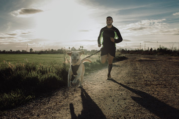 Man running with his dog on dirt road