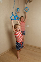 Two little sisters are engaged in gymnastic rings
