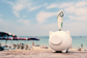 Piggy bank and money on table and sea background, concept save money to travel