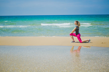 young mother stretching legs with lunge hamstring stretch exercise leg stretches. Fitness female athlete relaxing on beach doing a warm-up before her strength training cardio workout.