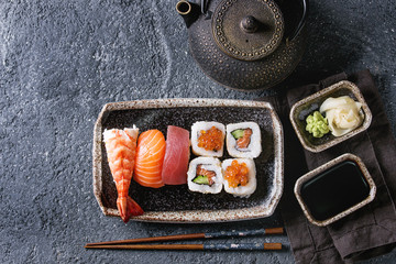 Sushi Set nigiri and sushi rolls in dark ceramic plate with soy sauce, iron teapot and chopsticks over black stone texture background. Top view with space. Japan menu