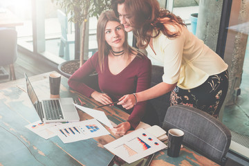 Two young businesswomen are discussing business plan.On desk is laptop, charts and diagrams.