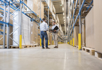 Two men with folder talking in factory warehouse