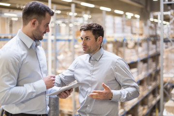 Two men with tablet talking in factory warehouse