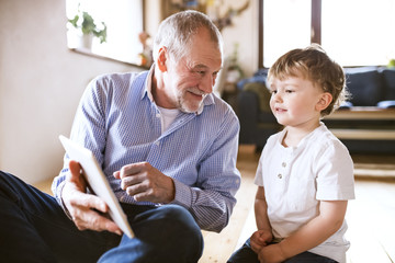 Grandfather and grandson sitting on floor, using digital tablet