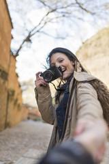 """Young tourist holding boyfriend hand in """"Cuesta del rey chico"""" near to """"La Alhambra"""" Granada, Spain"""