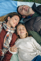 Happy family lying on blanket with closed eyes