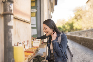 """Woman smelling spices and seasoning on an old street """"paseo de los tristes"""" in Granada, Spain."""