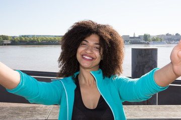 beautiful young woman smiling with curly hair makes a selfie with her smartphone phone