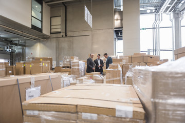 Three men in factory warehouse surrounded by cardboard boxes