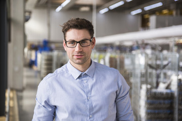 Portrait of confident businessman in factory shop floor