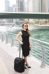 Attractive young business woman pulling suit case trough the magnificent city. Beautiful city scape panoramic view.