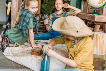 boy putting message in a bottle, two girls with map behind on porch, cute kids concept