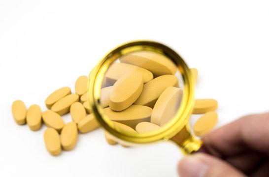Orange medicine tablet is being examinate by magnifier