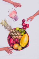 Hands and colorful mix of tropical fruits on white background