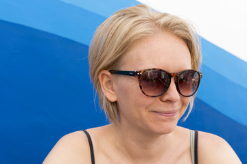 Smiling Woman Wearing Sunglasses Over Blue Waves Background