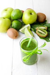 Green smoothie near ingredients for it on white wooden background. Apple, lime, spinach. Detox. Healthy drink.