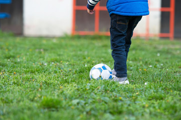 child boy playing football, shooting ball outdoor on grass