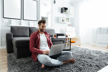 Smiling young man sitting indoors at home while using laptop