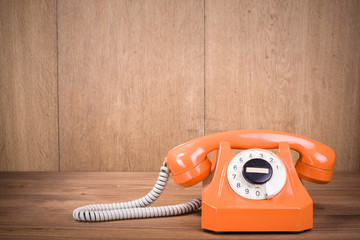 Orange retro telephone front wooden wall background