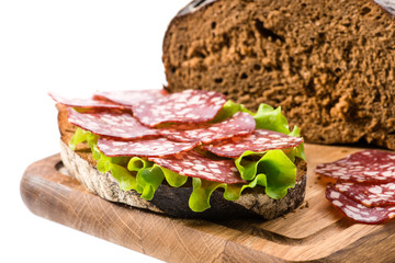 Bread and a sandwich with salami close-up