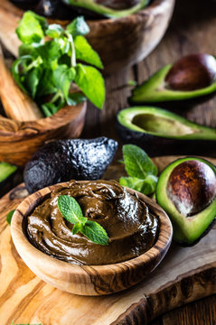Avocado chocolate mousse with mint in olive wooden bowl