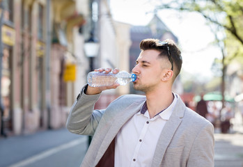 young business man drinking watyer from bottle on a street