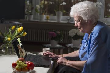 Seniorin sitzt im Wohnzimmer und schreibt Nachrichten am Laptop