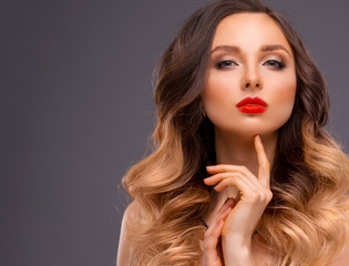 Studio Portrait of Beautiful Model with Volume Shiny Wavy Hair. Fashion Make Up and Curly Ombre Hair. Close up