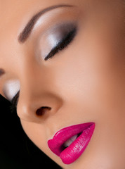 Beauty Close-up Portrait of Beautiful Sexy Woman Model with Grey Fashion Eyes Make-up and Pink Lips on Black Background. Bright Color