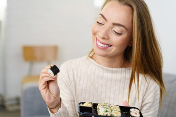 lächelnde junge frau genießt sushi zu hause