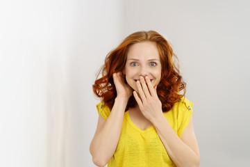 frau hält überrascht eine hand vor den mund