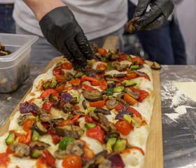 Cook's hands preparing big pizza