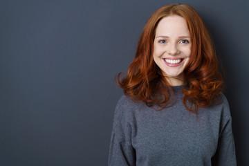 lächelnde frau mit roten haaren steht vor einer grauen wand