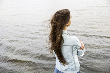 The dark-haired girl stands with her back near the pond. The wind blows the hair
