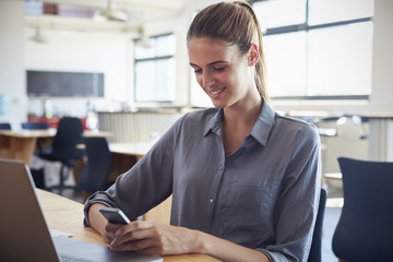 Happy young woman in office using smartphone