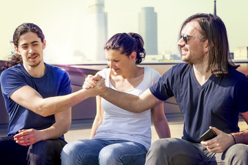group of three young friends shake hands on a london terrace