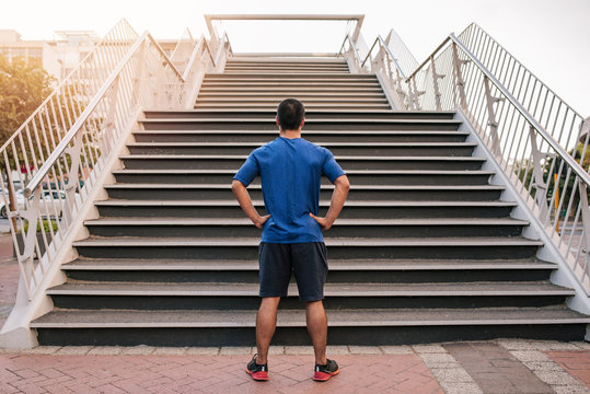 Young athletic man preparing to run up steep stairs